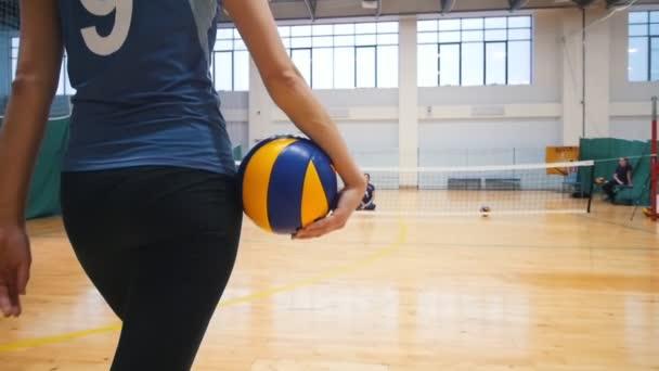Sport pro zdravotně postižené osoby. Trenér mladá žena chodí na její oddělení podržením volejbalový míč a sedí na podlaze