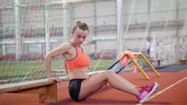 Mladý sportovní žena pracující pomocí lavice