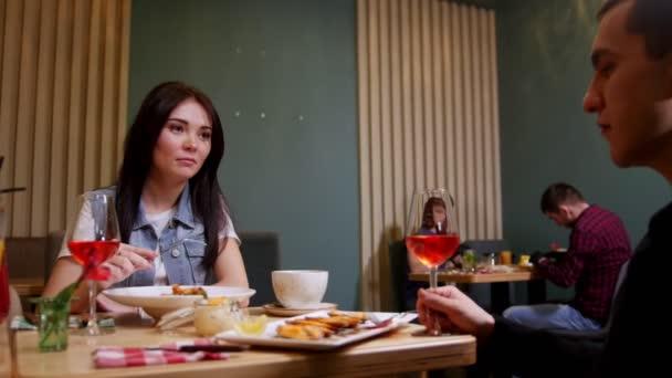 Mladý pár sedí u stolu v kavárně