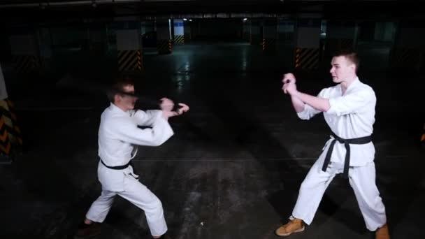 Két fiatal férfi kimonó képzés egy parkolóban. Kard küzdelem