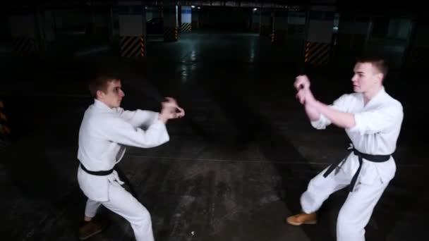 Két fiatal férfi kimonó képzés tudásukat egy parkoló. Kard küzdelem