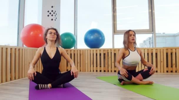 Mladé ženy sedí na jógu rohože a dělat dechová cvičení