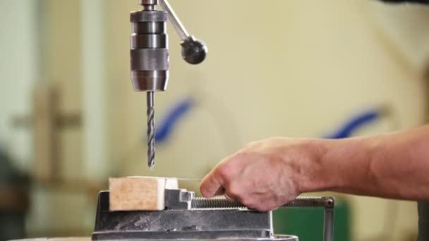 Velký průmyslový vrtné stroj. Vrtání se přiblíží k kovové desce a vyvrtne