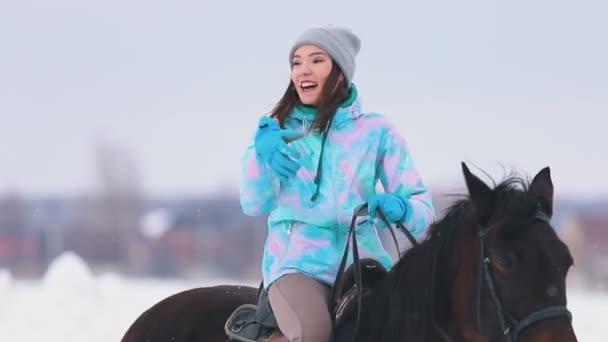 eine aufgeregte junge Frau auf dem Pferderücken im Gespräch mit ihrem Freund