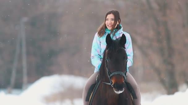 Egy mosolygó fiatal nő-lovon a téli erdőben