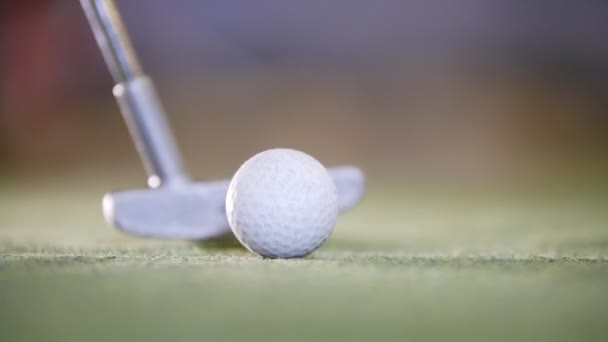 Playing mini golf. The golf stick hitting a golf ball. Close up