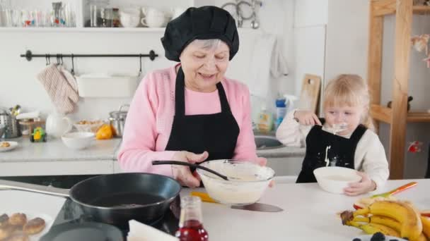 Family making pancakes. An old woman putting the dough on the pan