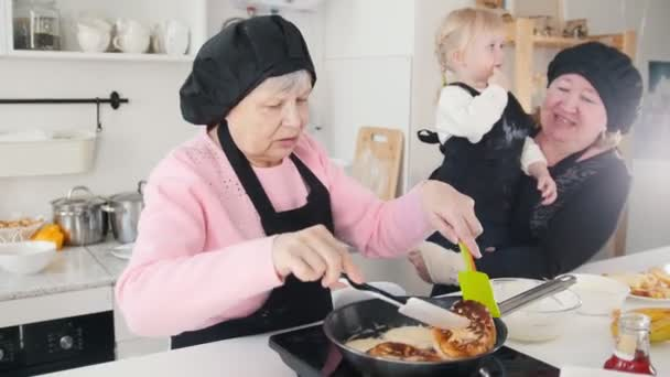 An old woman making pancakes in the kitchen and another old woman holding a little girl on her hands