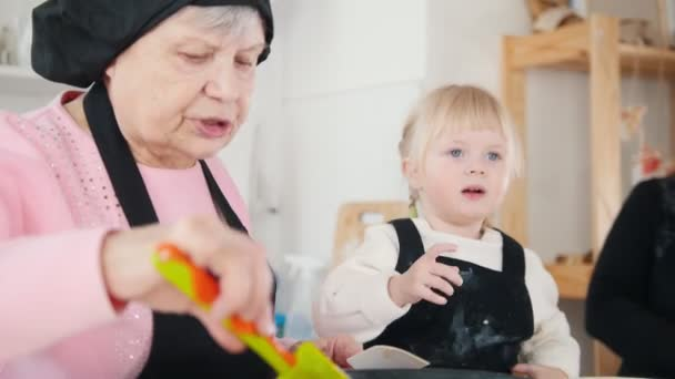 An old woman making pancakes in the bright kitchen and talking with a little girl