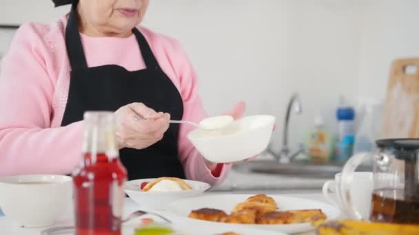 An old woman eating pancakes. Putting sour cream on the top of pancakes
