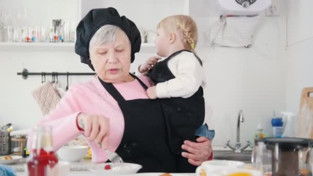 An old woman eating pancakes with a sour cream and holding a little girl on her hands