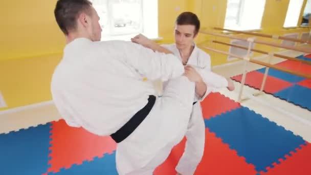 Bojová umění. Dva atletické muže, kteří cvijí své schopnosti aikido. Ochrana před zasažencem a vrhnáním protivníka na podlahu