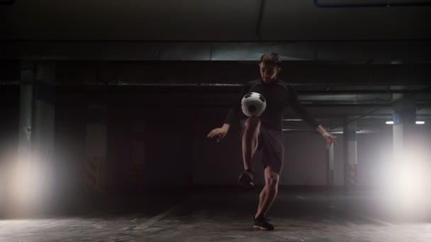 Egy fiatal futball-ember képzés trükkök a labdát. Kiegyensúlyozzák a labdát a hátán