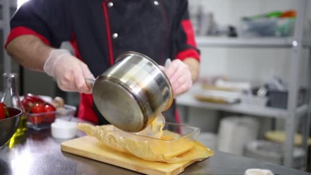 ein Koch in der Küche. Die Brühe in eine Glasschüssel gießen