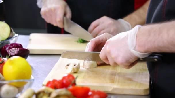 ein Koch in der Küche. Champignons für die Portion schneiden