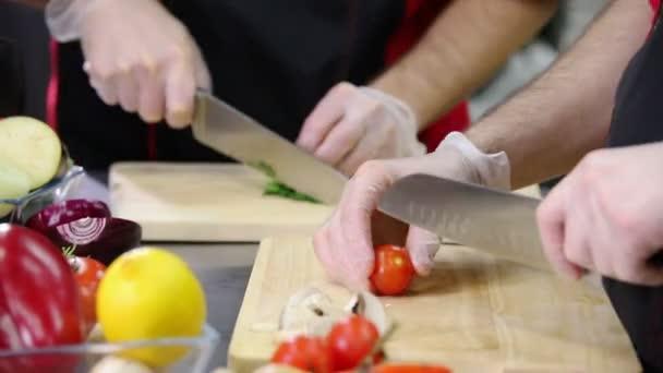 Kuchař v kuchyni, který krájí rajče na servírovací