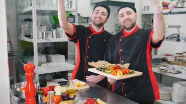 Restaurant kitchen. Two men chefs finished serving dishes with a bellissimo gesture