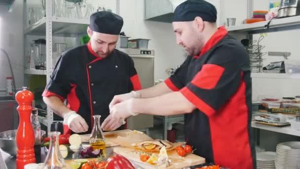 Restaurantküche zwei männliche Köche beim Servieren von Fischgerichten am Schneidebrett