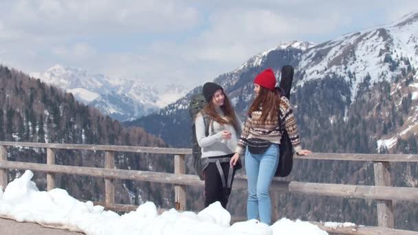 Dvě mladé ženy na cestách na Dolomity s velkým batohu a kytarou. Stojí na silnici a mluví