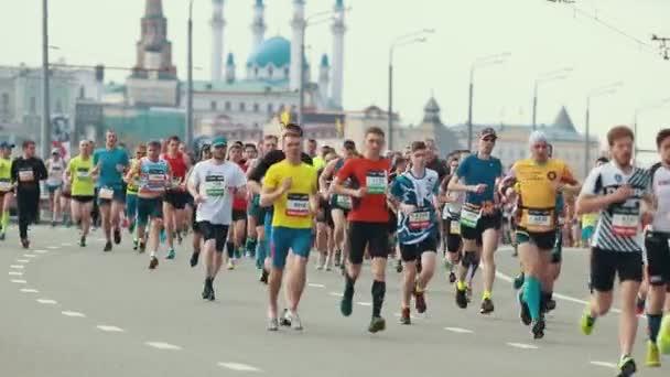 05-05-2019 RUSSIA, KAZAN: A running marathon. People running on the side of the road on a background of Kazan Kremlin