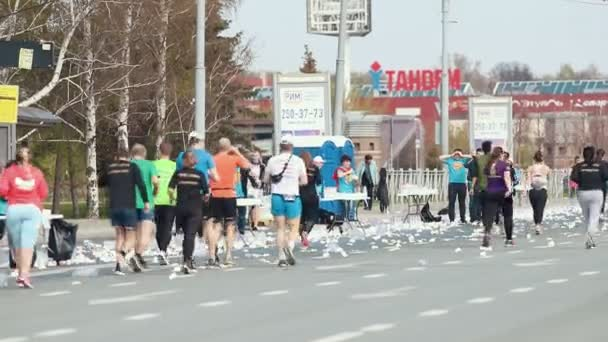 05-05-2019 RUSSIA, KAZAN: A running marathon in the city. A crowd of people running on the road and taking water from volunteer