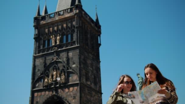 Dvě ženy stojící na pozadí Bridge Tower Charlese Bridge, které drží mapu a hledají způsob, jak jít