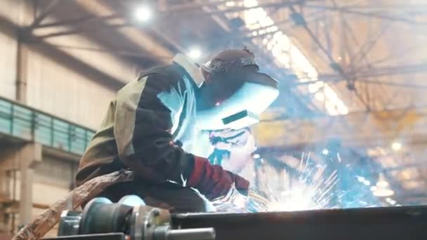 Construction plant. A man worker in a helmet using a welding machine on metal detail. Fire sparkles