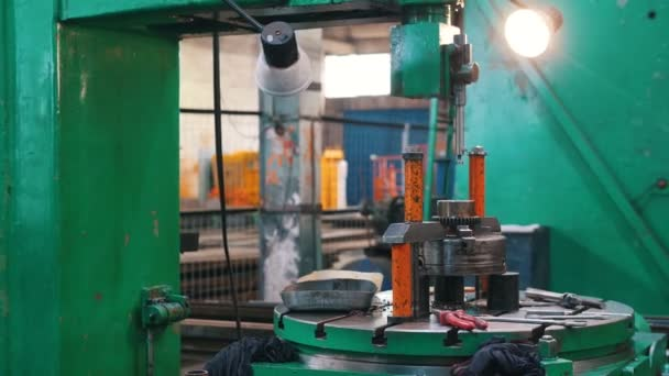 Working machine Metal rod falls on the material and rises. The camera moves from right to left.
