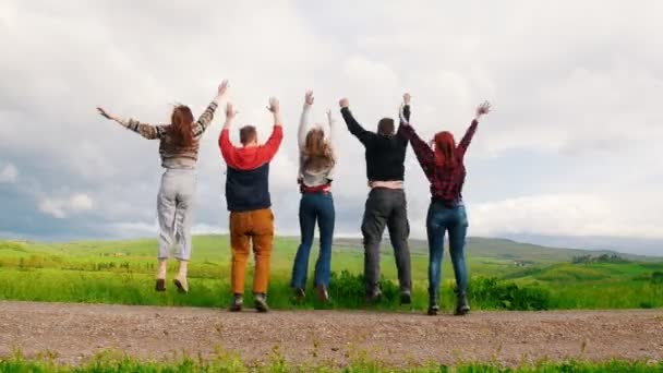 Five young friends are jumping holding hands on a green field.