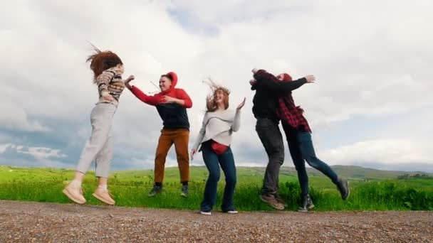 Five young people jump and smile on the green field