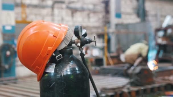 A piros sisak van a gázpalack-ember dolgozik hegesztőgép a háttérben a növény