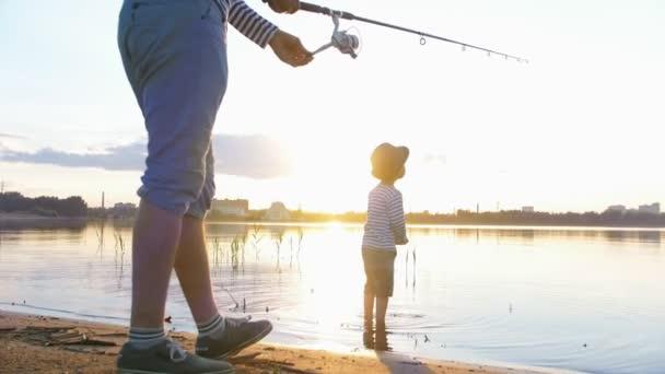 Egy apa és fia a halászat együtt-egy ember, aki a rúd és a halászat és fia állt a tengerparton-naplemente