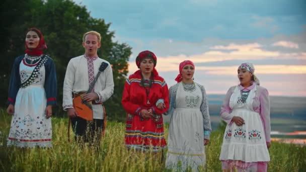 Menschen in traditioneller Tracht gehen auf das Feld und singen ein Lied - Sonnenuntergang