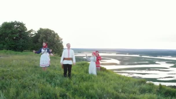 People in traditional Russian clothes singing and dancing at the green hill - Camera smothly moves around they