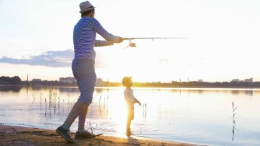 Father and son fishing on the shore of the river at sunset