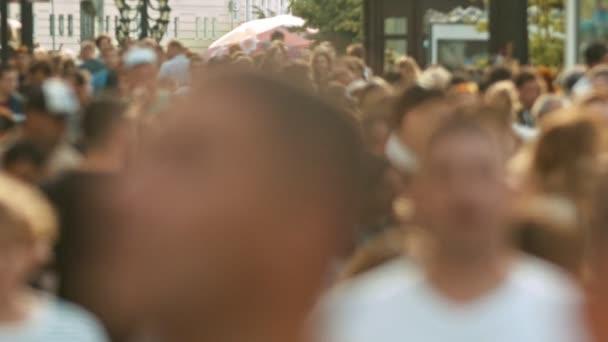 Velký dav lidí, kteří chodí po ulicích