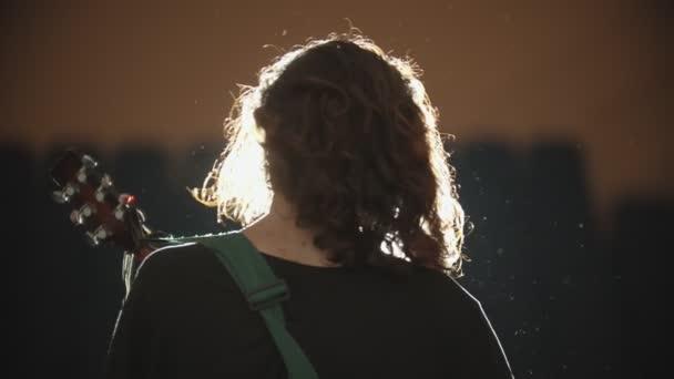 Mladý muž s dlouhými vlasy hrající si na vystoupení písničku