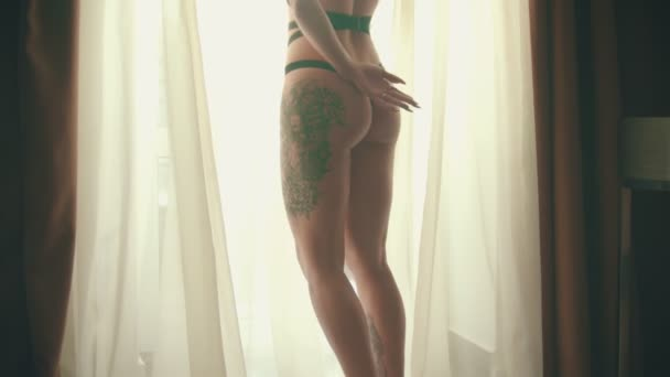 Young woman with tattoos in a sexy black underwear standing in front of the window in hotel room