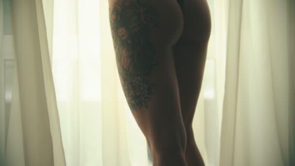 Mladá žena s tetování v sexy černém spodním prádle, stojící před oknem v hotelovém pokoji a dotýká se štíhlé postavy