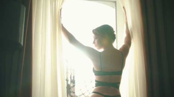 Fiatal tetovált nő egy szexi fekete fehérnemű előtt álló ablak a szállodai szobában, és megnyitja a függöny-fényes nappali