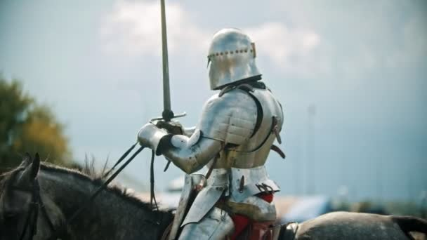 A man knight riding a horse around the battlefield and greeting the people watching behind the fence - raises his hand up in the sky holding a sword