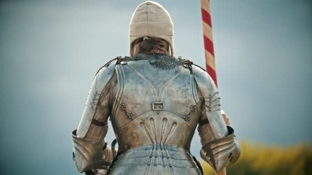 A man knight in the armor holding a spear