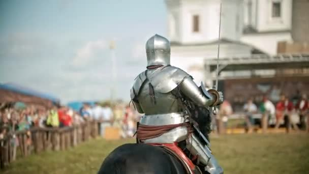 BULGAR, RUSSIA 11-08-2019: Knights with swords riding horses on the battlefield and crossing their swords - people watching behind the fence
