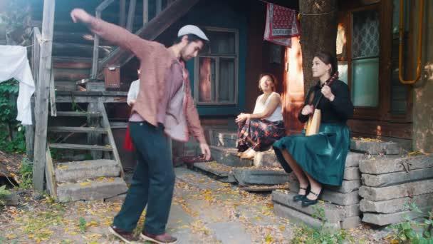 Vousatý muž tančící ruský lidový tanec-ženy sedící na schodech blízko venkovského domu-žena hrající balalajka