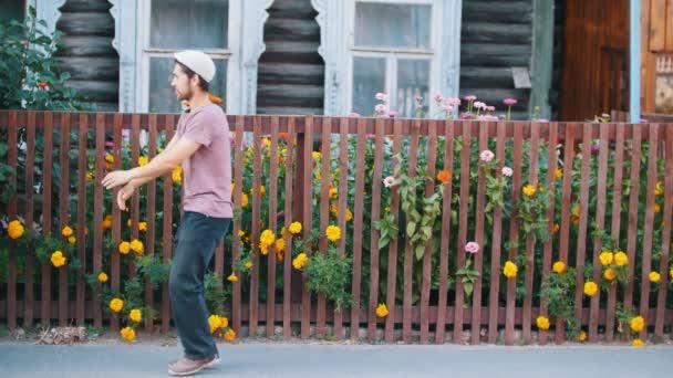 Ruský muž tancující ruský lidový tanec u plotu s květinami