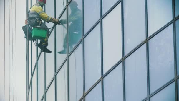 Muž pracující ve žlutých pracovních šatech zavěšený na provazech a otírá vnější okna obchodního mrakodrapu ze špíny - průmyslového alpinismu - zataženého počasí