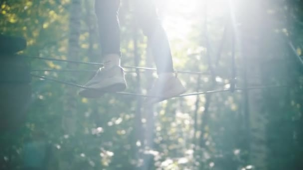 A little girl walking on the rope - an entertainment attraction in the green forest