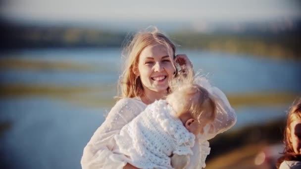 Mladá usměvavá žena drží své dítě, zatímco stojí v přírodě