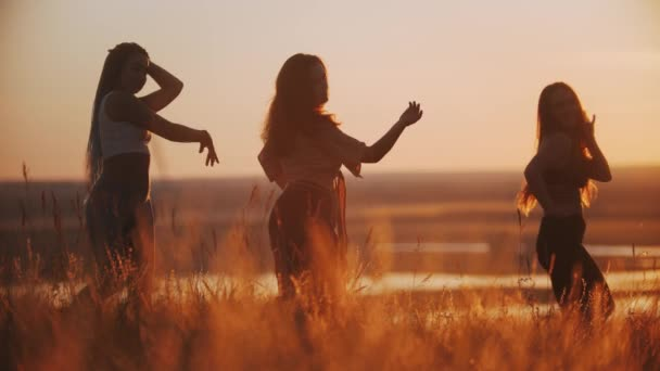 Three young women doing aerobic dance and slow movements with their hands on sunset