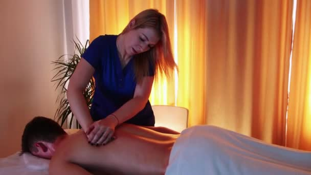 Massage session in the spa centre - woman doctor massaging her clients back
